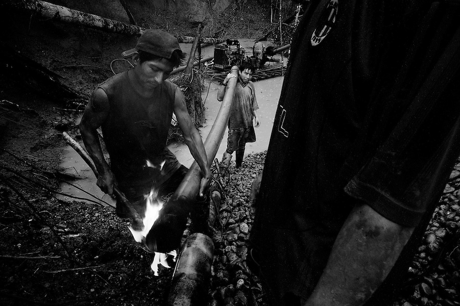 In the jungle near Laberinto Island, Peru, Feb. 8, 2007 - A trio of miners work to repair a pipe used for blasting the pits.