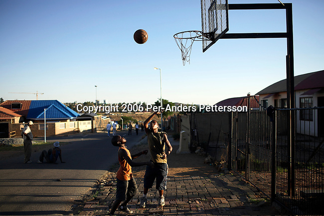 SOWETO, SOUTH AFRICA OCTOBER 24: Boys play basket ball in the street as the sun goes down October 24, 2006 in the Orlando West section of Soweto, Johannesburg, South Africa. Soweto is South Africa?s largest township and it was founded about one hundred years to make housing available for black people south west of downtown Johannesburg. The estimated population is between 2-3 million. Many key events during the Apartheid struggle unfolded here, and the most known is the student uprisings in June 1976, where thousands of students took to the streets to protest after being forced to study the Afrikaans language at school. Soweto today is a mix of old housing and newly constructed townhouses. A new hungry black middle-class is growing steadily. Many residents work in Johannesburg but the last years many shopping malls have been built, and people are starting to spend their money in Soweto.  .(Photo by Per-Anders Pettersson/Getty Images).