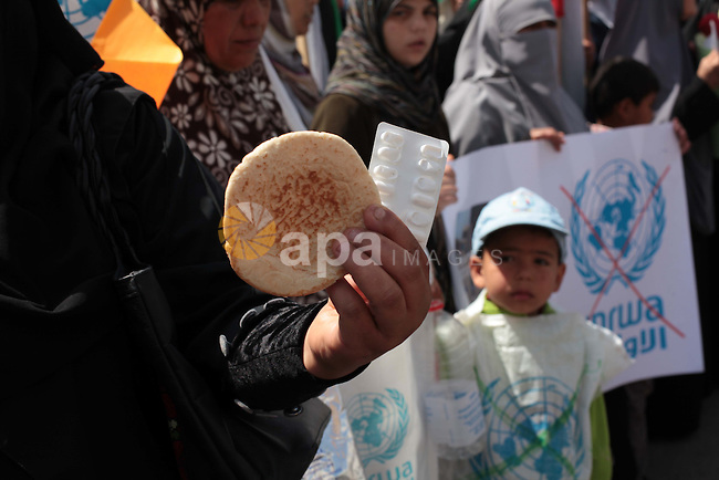 Palestinian women take part in a protest against the decision made by the United Nations Relief and Works Agency (UNRWA) to reduce food aid delivered to the Gaza Strip in front of the UNRWA headquarters in Gaza City on April 9, 2014. Photo by Ashraf Amra
