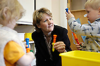 Lynn Edlefson, coordinator of the Office of Campus Child Care, stops by the UW Infant Toddler Center to play with the children there, including 2-year-olds Alekha Jolly (left) and Will (last name withheld, right). Edlefson, a 2004 Academic Staff Excellence award recipient, was instrumental in creating the center.<br /> <br /> Client: University of Wisconsin-Madison<br /> &copy; UW-Madison University Communications 608-262-0067<br /> Photo by: Michael Forster Rothbart<br /> Date:  4/04    File#:   D100 digital camera frame 2747.