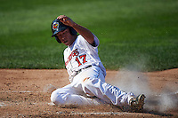 Rochester Red Wings third baseman Doug Bernier (17) slides safely into home during a game against the Indianapolis Indians on June 10, 2015 at Frontier Field in Rochester, New York.  Indianapolis defeated Rochester 5-3.  (Mike Janes/Four Seam Images)