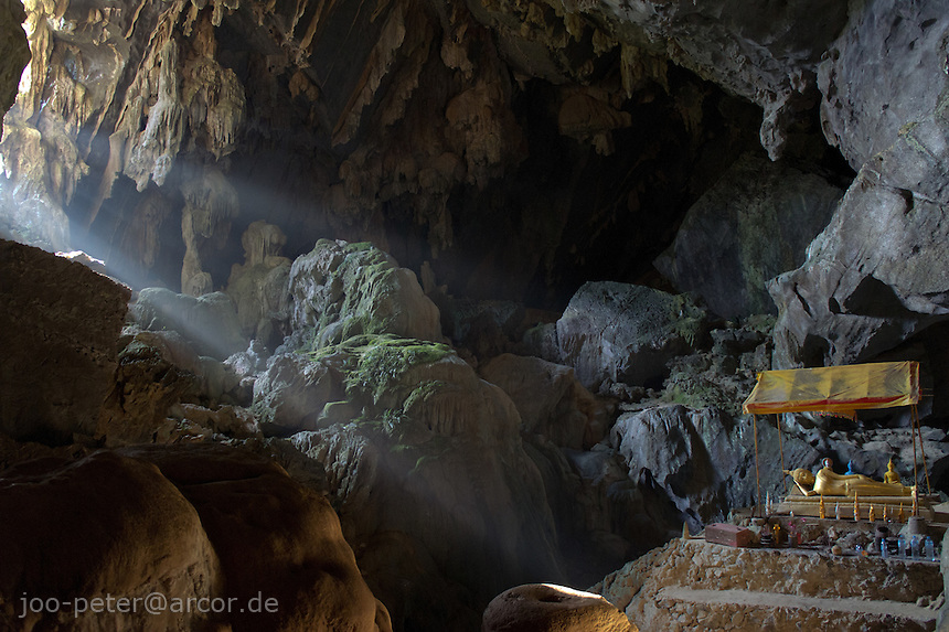 sunshine beams enter Poukham cave, shining on Buddha shrine, close to Vang Vieng, Laos, 2012. The cave is also spelled  Tham Pu Kham or Tham Pou Kham in latin  letter writing, meaning cave of the golden crab. Like in many caves of  Laos, there is a buddhist shrine inside.