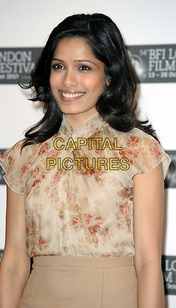 FREIDA PINTO  .The 'Miral' press conference & photocall, London Film Festival, Vue West End, Leicester Square, London, England..October 18th, 2010.half length beige skirt top blouse silk satin floral print .CAP/WIZ.© Wizard/Capital Pictures.