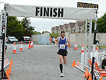 Colin Costello crosses the line to win the Newtown Blues 12.5K run. Photo:Colin Bell/pressphotos.ie
