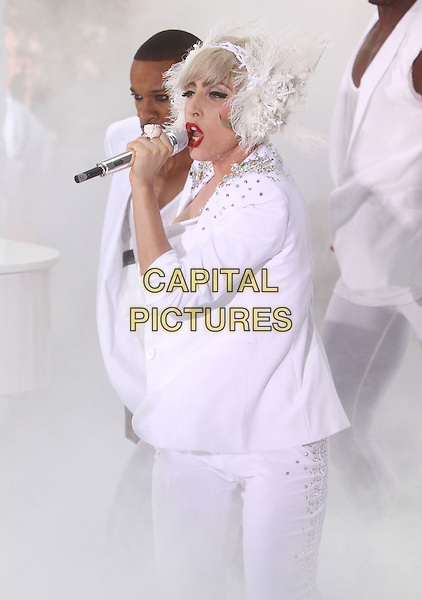 "LADY GAGA (Stefani Joanne Angelina Germanotta) .performs live on NBC's ""TODAY"" Show at Rockefeller Center, New York, NY, USA, 9th July 2010..on stage music concert gig half length white microphone singing suit jacket bra feather lace ear muffs head band hair hairband silver beaded studded embellished .CAP/ADM/AC.©Alex Cole/AdMedia/Capital Pictures."