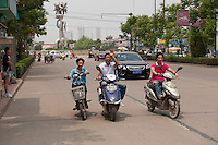 Daytime landscape view of three boys riding scooters on a road in Bozhou in Qiáochéng Qū in Anhui Province.  © LAN
