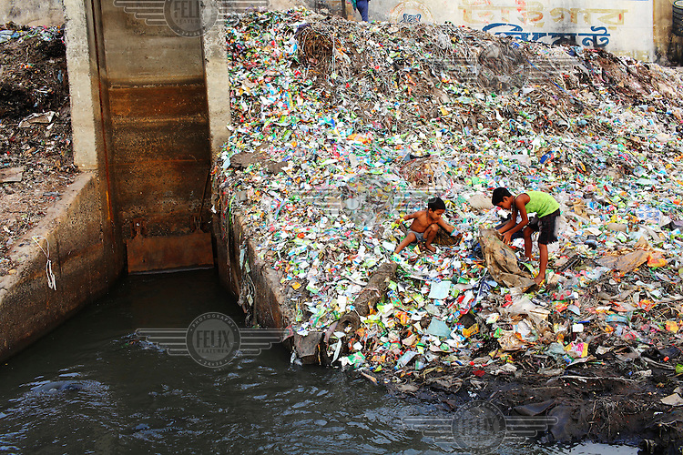Two young boys collect recyclable items from among the piles of rubbish dumped along the banks of the Buriganga River. Everyday 1.5 million cubic metres of waste water from 7,000 industrial units in surrounding areas and another 0.5 million cubic metres from other sources are released into the river. Although the government have enacted laws that require industry to safely process effluents these are rarely enforced and pollution remains uncontrolled. The river is biologically dead and increasingly a serious health hazard to those using and living near it.