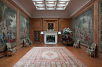 A spacious music room, its walls clad with wood panelling, the carved details also frame floor-to-ceiling tapestries