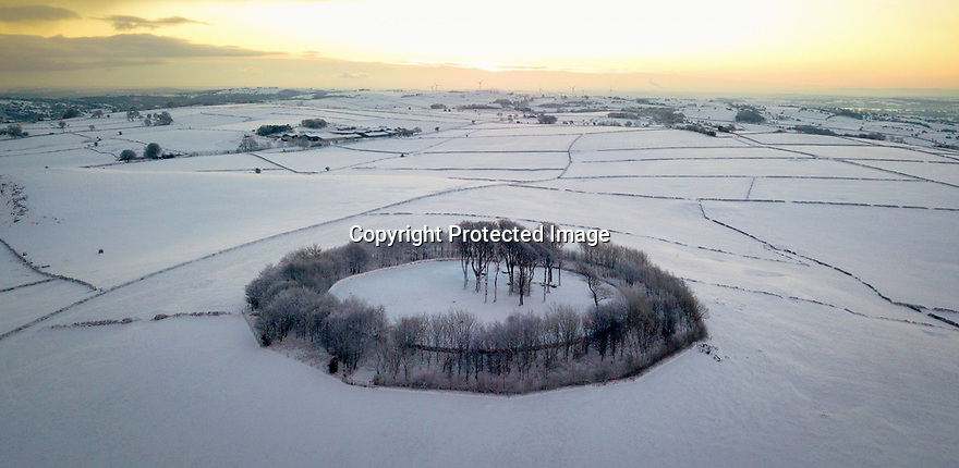 30/01/19<br /> <br /> Snow showers drift in as dawn breaks over a neolithic burial mound and ring of trees in the Derbyshire Peak District near Parwich kknown as Minninglow. <br /> <br /> Minninglow is the largest and most prominently sited cairn in the Peak District. Surrounded by a beech plantation 500m to the east of The High Peak Trail between the villages of Parwich and Elton, it is a landmark for miles around. <br /> <br /> Measuring 34m by 44m, the cairn consists of at least four chambers and has undergone a number of construction phases. The Low originally began life as a single chamber with a small mound comprised mainly of limestone probably during the Neolithic period. It was later covered by a long cairn with four chambers and later still converted into a massive circular mound, perhaps during the Bronze Age. <br /> <br /> Shot with a drone with permission from landowner by Rod Kirkpatrick who holds a PfCO and drone insurance.<br /> <br /> All Rights Reserved, F Stop Press Ltd.  (0)7765 242650  www.fstoppress.com rod@fstoppress.com