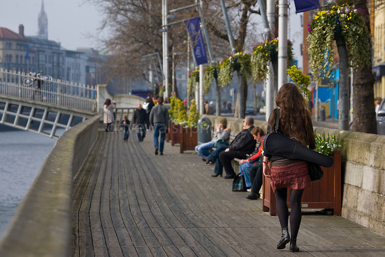 Red haired girl walking down the Liffey Boardwalk towards Ha'penny Bridge, Dublin, carrying violin case