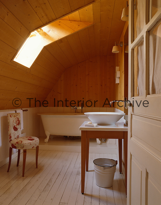 An antique clawfoot bath is situated at one end of a long attic bathroom lit by a skylight and covered in pine tongue-and-groove