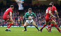 Pictured: Jared Payne of Ireland (C) is trying to avoid Jamie Roberts (L) and Leigh Halfpenny (R) of Wales Saturday 14 March 2015<br />