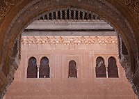 Wall in carved stucco with latticed windows seen through a horseshoe arch in the Patio of the Gilded Room, between the Mexuar and the Gilded Room or Cuarto Dorado in the Comares Palace, Alhambra Palace, Granada, Andalusia, Southern Spain. It was built under Mohammed V in the 14th century. The Alhambra was begun in the 11th century as a castle, and in the 13th and 14th centuries served as the royal palace of the Nasrid sultans. The huge complex contains the Alcazaba, Nasrid palaces, gardens and Generalife. Picture by Manuel Cohen