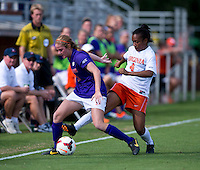 Morgan Stith (4) of Virginia tries to poke the ball away from Abby Jones (21) of Clemson at Klockner Stadium in Charlottesville, VA.  Virginia defeated Clemson, 3-0.