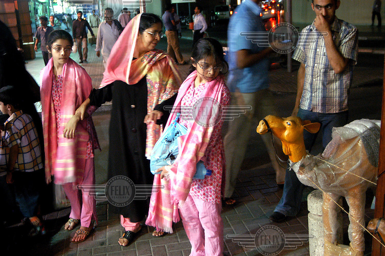 A South Asian family look at a toy camel being sold in a Dubai souk..