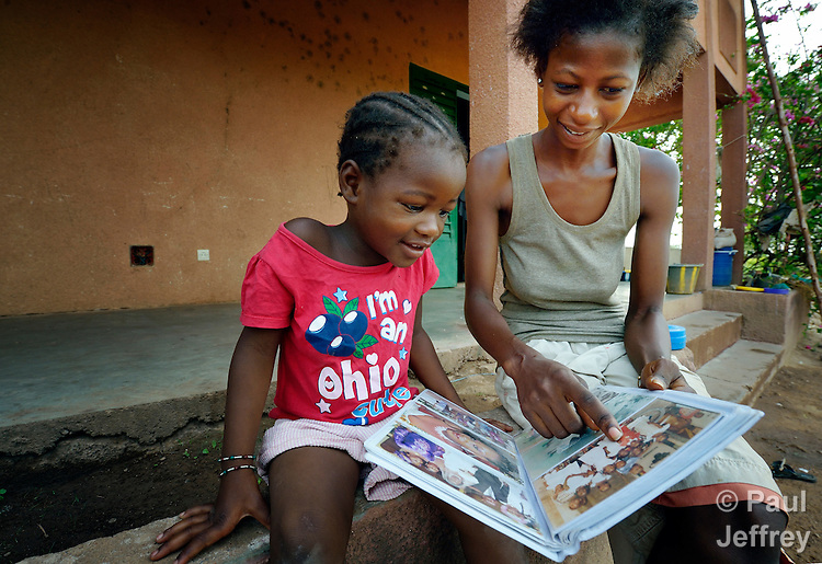 Three-year old Naomi Wallet Tafaki and her 21-year old sister Monique Kone look at an album of family photographs in a Catholic training center in Niamana, Mali. Several families displaced by the fighting in northern Mali took refuge in the center, and have received support from the ACT Alliance.
