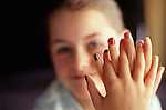 Young girl ( 8 years old) showing off her newly painted multicolored finger nails smiling at camera Bothell Washington State USA MR