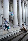 A man speaks on the phone while a pedestrian walks past him at the Grand Post Office in BBD Bagh in Kolkata, West Bengal  on Friday, May 26, 2017. Photographer: Sanjit Das