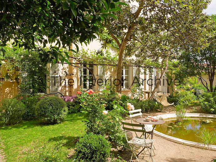 Garden furniture is grouped around the pond in this sunlit garden