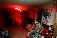 Catie Lutz (red jacket) and Sean Leonard, drummer for suburban Chicago band Vacation Bible School, sit on a couch at the end of a punk show in the basement of the White House in Woodstock, Illinois.  The White House was a small suburban residential home rented by a group of 20-somethings in Woodstock, Illinois, a distant northwestern suburb of Chicago.  For about a year, the renters of the house staged punk-rock concerts in the house's small basement, without the approval of the neighborhood, local government, or police.  .