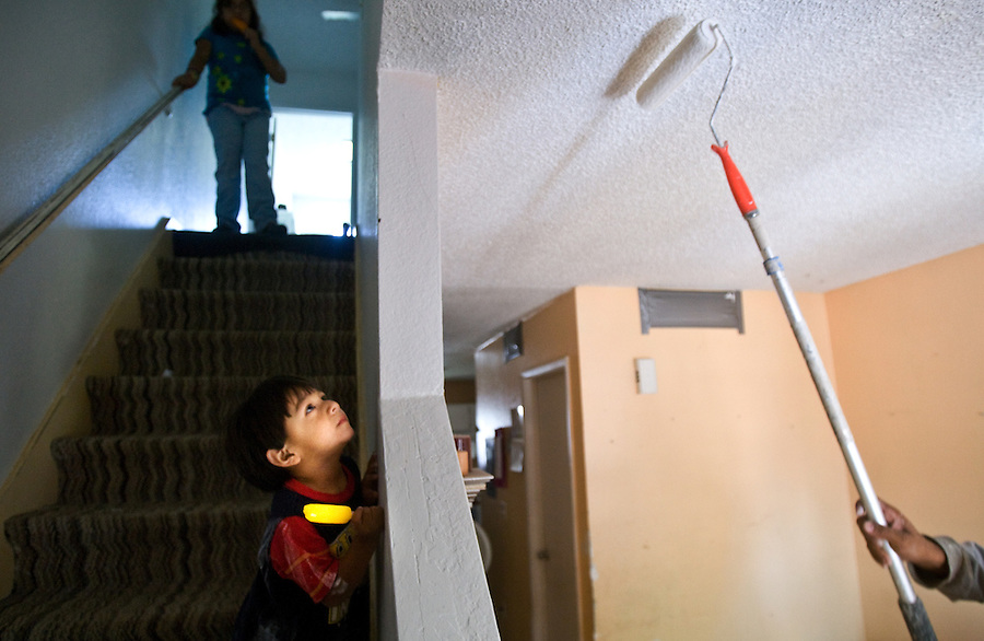leaving0627 Christian Sanchez, 2, watches a friend of his family paints the ceiling of their West Valley home.  (Pat Shannahan/ The Arizona Republic)