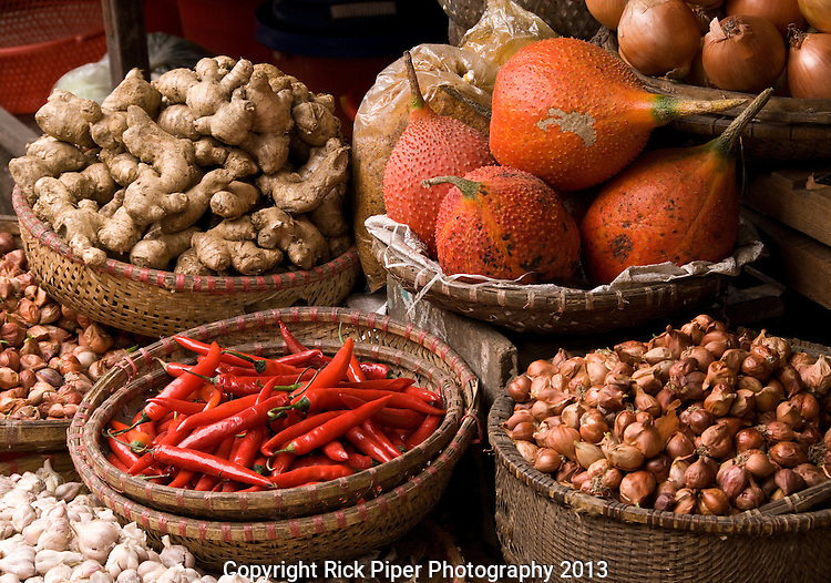 Gac Fruit 01 - Baskets of gac fruit, chilli, onions, shallots, ginger and garlic at a market in the Hanoi Old Quarter, Viet Nam.