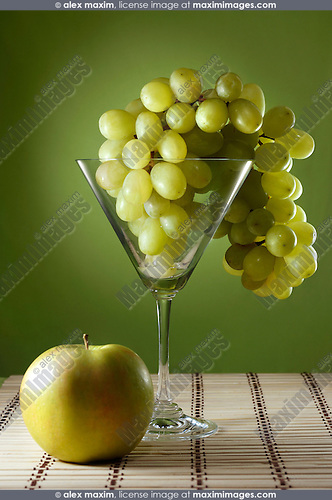 Grapes in a martini glass and an apple food still life
