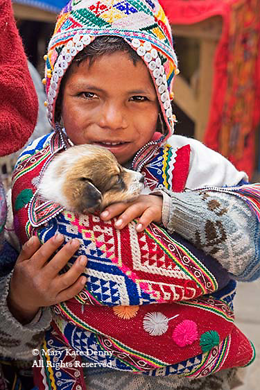 Peruvian young girl in hand embroidered costume dress and hat holds puppy close to her.