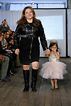 Fashion designer walks runway with child model at the close of her Belle Threads collection fashion show, during the KidFash Magazine runway show in Brooklyn, New York on Nov 4, 2017.