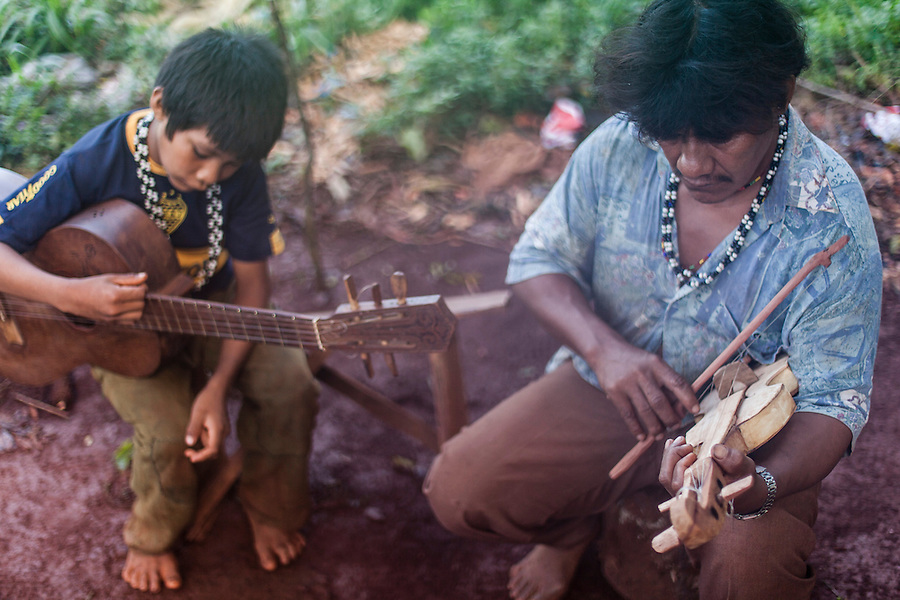 Angel Morinigo, an Mbya Guarani craftsman and musician from Andresito village near San Ignacio, Misiones, Argentina, playing traditional Guarani folk music with his son.