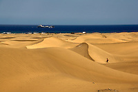 Tourist walking across sand dunes, with tanker at sea in the background at Maspalomas, Gran Canaria,Canary Islands, Spain