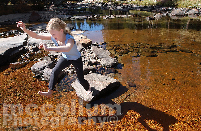 Outdoor enthusiast and camper Katie McCollum jumps across the Tuolumne River, located in , Tuolumne Meadows, Yosemite National Park.