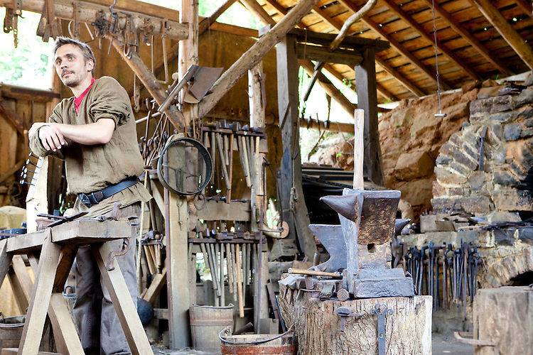 The blacksmith of the Guedelon Castle, a medieval construction project in Treigny, France, on June 14, 2010.  <br /> <br /> The intent of the project, begun in 1997 by Michel Guyot, is to build a completely functioning 13th century medieval castle using only tools and techniques of that era.  Additionally all raw materials are taken from the surrounding countryside, which includes a quarry.  Over 40 people are employed by the project, as well as more than 100 volunteers.  The site has become the biggest tourist attraction in the French department of Yonne, with more than 200,000 people visiting annually.