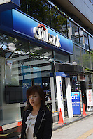 A young lady is passing in front of American mega bank, Citibank in Tachikawa, Tokyo, Japan.