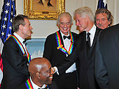 John Paul Jones of Led Zeppelin, one of the seven recipients of the 2012 Kennedy Center Honors, shakes hands with former United States President Bill Clinton as fellow honorees Jimmy Page, Robert Plant and Buddy Guy look on as they prepare to pose for a photo following a dinner hosted by United States Secretary of State Hillary Rodham Clinton at the U.S. Department of State in Washington, D.C. on Saturday, December 1, 2012.  The 2012 honorees are Buddy Guy, actor Dustin Hoffman, late-night host David Letterman, dancer Natalia Makarova, and the British rock band Led Zeppelin (Robert Plant, Jimmy Page, and John Paul Jones)..Credit: Ron Sachs / CNP