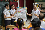 Nursing students from the Mary Johnston College of Nursing talk with parents in the Parola neighborhood of Tondo, a poor section of Maniila, Philippines. The students regularly visit the neighborhood to do health education and monitor the health of residents, at the same time running  a feeding program for neighborhood children. As the children eat, the students talk about nutrition and health with their parents. <br /> <br /> The nursing school is supported by United Methodist Women.