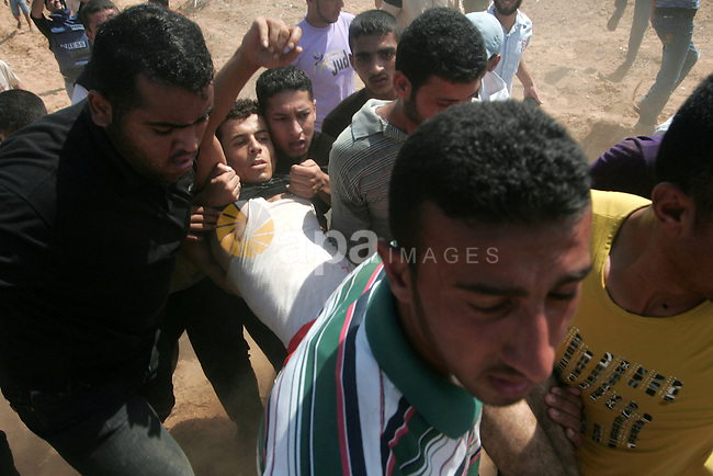 Palestinians carry a wounded man during a protest against the Israeli blockade near the border between Israel and the Gaza Strip , in east of Khan Younis, southern Gaza City on Sept. 26,2010 . Israel and neighboring Egypt have kept Gaza under blockade since the militant Hamas seized power in Gaza in June 2007. Photo By Khaled Khaled