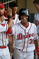 Left fielder Lorenzo Cedrola (35) of the Greenville Drive is greeted after scoring a run in a game against the Kannapolis Intimidators on Wednesday, May 9, 2018, at Fluor Field at the West End in Greenville, South Carolina. Kannapolis won, 10-2. (Tom Priddy/Four Seam Images)