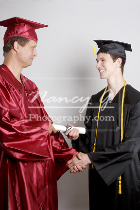 A Dean shaking hands with a graduate receiving a diploma