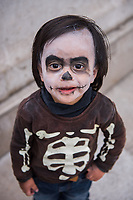 Mexico, Mexico City. Day of the Dead, Dia de los Muertos. People painting their faces, boy dressed as a skeleton.