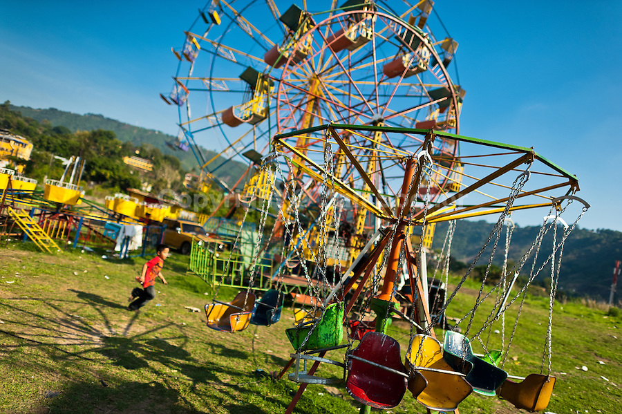 Vintage chain carousel and a ferris wheel seen at a village fair in the countryside close to San Salvador, El Salvador, 7 May 2011.