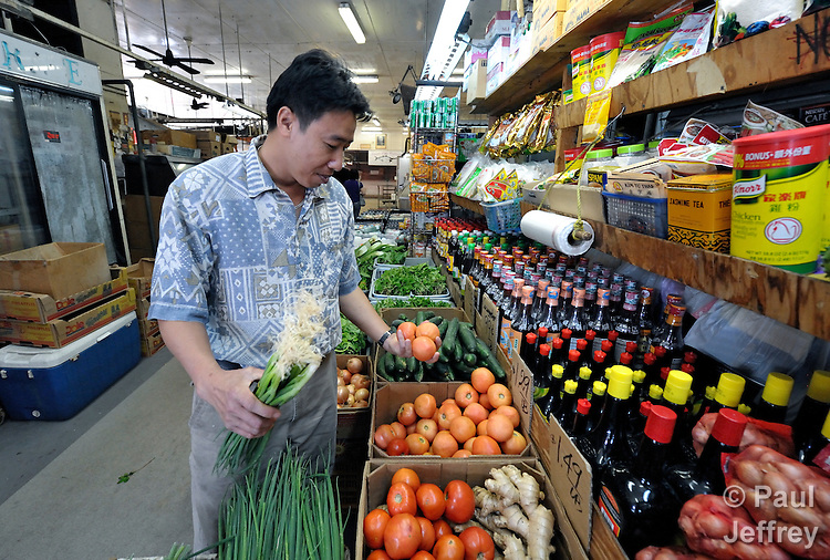 Hieu Van Bui, a Vietnamese survivor of human trafficking, shops for food in a market in the Chinatown neighborhood of Honolulu, Hawaii. He has received assistance from the Susannah Wesley Community Center, which has played a key role in identifying and supporting victims of trafficking in Hawaii.