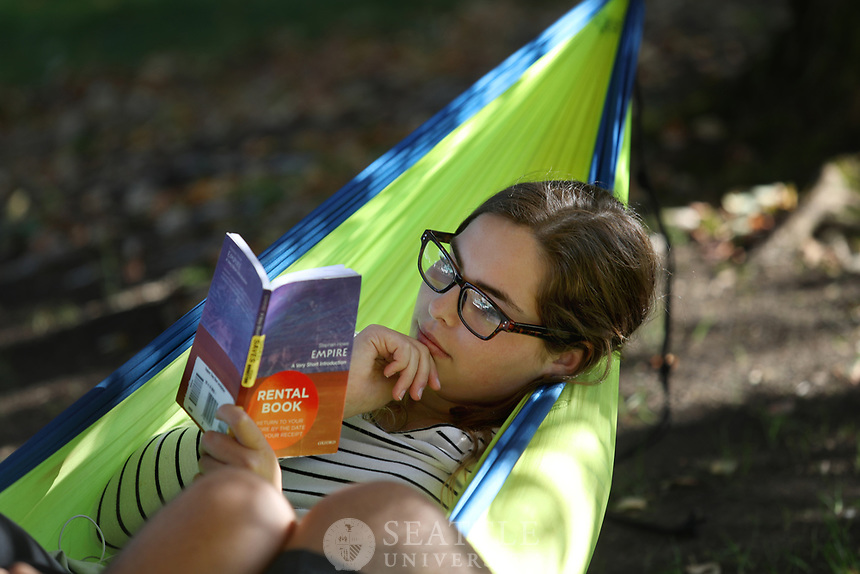 """September 28th 2016 - Seattle University freshmen Katherine Murphy, of Mulkoteo, WA and Benjamin Trujillo, of Boulder, CO get a start studying for their Fall classes while relaxing in a hammock they set up outside Pigott and the Chapel of St. Ignatius. Murphy is studying mechanical engineering and Trujillo is studying physics at Seattle U. """"It's nice out and why not be in a hammock,"""" Murphy said. """"It's a Boulder thing to do,"""" Trujillo added."""