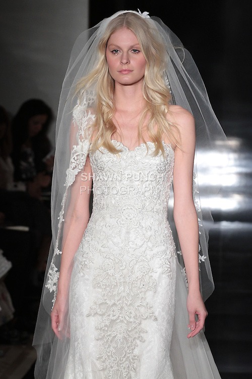 Model walks runway in a Chantilly lace fit and flare gown with embroidered detachable organza overskirt with matching veil, from the Reem Acra Spring 2017 bridal collection, during New York Bridal Fashion Week Spring Summer 2017, on April 15, 2016.