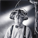 humorous photo of man, curator at Museum of Questionable Medical Devices, wearing device called the Psychograph on his head