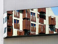Amsterdam IJ-Dock. Balkons met metalen hekken, weerspiegeld in een gebouw aan de overzijde van de straat