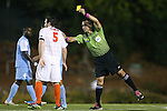 08 October 2013: Referee Hilario Grajeda (right) shows the yellow card to Clemson's Thomas McNamara (5). The University of North Carolina Tar Heels hosted the Clemson University Tigers at Fetzer Field in Chapel Hill, NC in a 2013 NCAA Division I Men's Soccer match. Clemson won the game 2-1 in overtime.