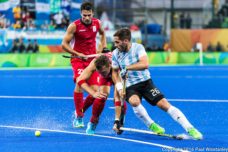 Agustin Mazzilli #26 of Argentina protects the ball against defenders Loick Luypaert #25 of Belgium and Simon Gougnard #22 of Belgium during Argentina vs Belgium  in the men's gold medal game at the Rio 2016 Olympics at the Olympic Hockey Centre in Rio de Janeiro, Brazil.