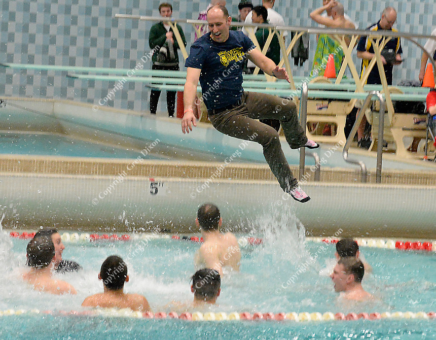 Madison West head coach, Bill Weaver, jumps into the water to celebrate with his team for their first place victory in the Wisconsin Division 1 state championship swimming and diving meet at the UW Natatorium on Saturday, 2/17/18 in Madison