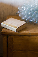 An antique book on a simple wooden bedside table